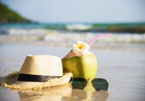 Fresh coconut with hat and sun glasses on clean sand beach with sea wave background - fresh fruit with sea sand sun vacation background concept