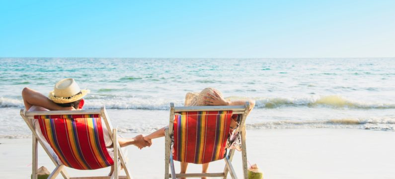 Relax couple lay down on beach chiar with sea wave background - man and woman have vacation at sea nature concept