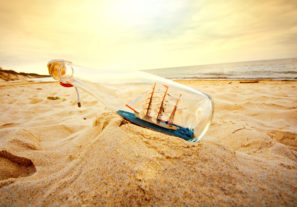 Ship in the bottle lying on the beach. Souvenir conceptual image. Nature in paradise.